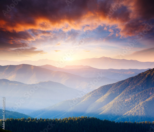 Wall mural Picturesque sunset in the summer mountains. Evening light illuminates the valley.