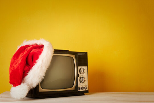 retro television with christmas hat on yellow background