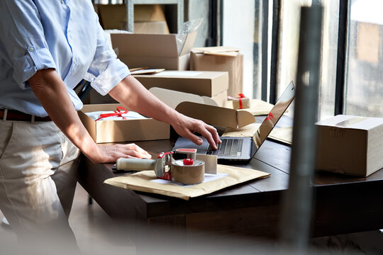 Female online store small business owner entrepreneur seller packing shipping ecommerce box checking website retail order using laptop preparing delivery parcel on table. Dropshipping concept. Closeup