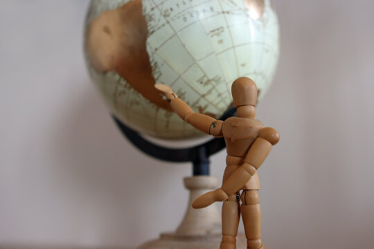 Close up of mannequin pointing at globe. The wooden puppet standing in front of the world with copy space.