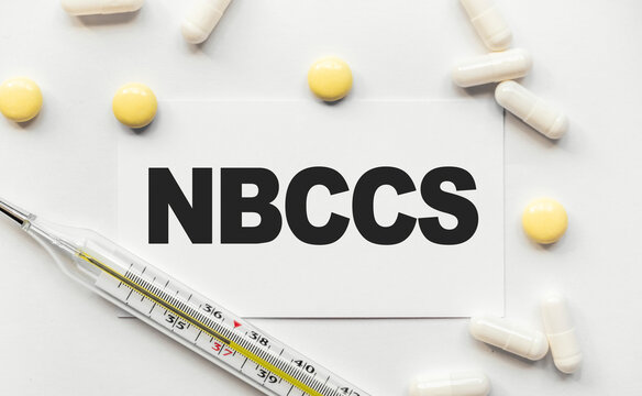 On white business card the inscription NBCCS Nevoid basal cell carcinoma syndrome. Near tablets and capsules. Thermometer with high temperature. Medical concept. Disease, treatment and prevention