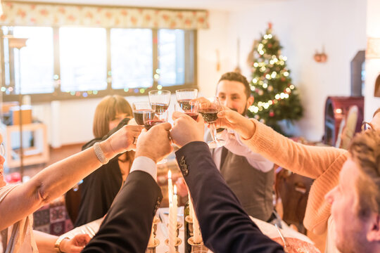 Family toasting and celebrating Christmas and New Year at home - Six people group at home around the table cheering with wine glasses during holidays and respecting coronavirus lockdown rules