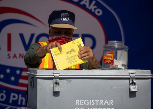 An election worker places mail-in ballots into a voting box at a drive-through drop off location at the Registrar of Voters for San Diego County in San Diego, California
