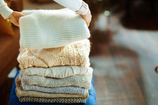 Closeup on elegant woman prepare sweaters pile for storage