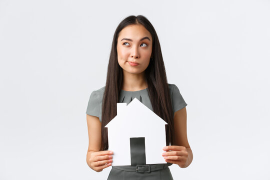 Insurance, loan, real estate and family concept. Thoughtful and doubtful asian woman thinking about buying new apartment, holding paper house and looking away, pondering, making decision