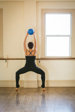 Woman doing exercise with ballet barre and exercise ball in dance studio. Two arms raised holding blue ball.