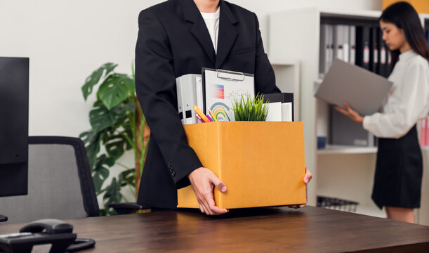 Businessman packaging and holding brown cardboard box with documents and personal office supplies because fired from work.