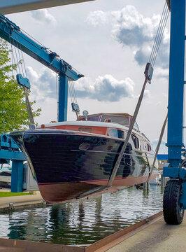 vintage wooden boat in marina slip suspended in boat lift sling