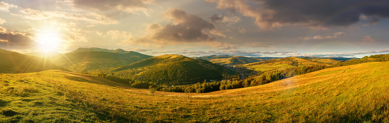 mountainous countryside landscape at sunset. panorama of a grassy rural field on the hill in evening light. village in the distant valley. clouds on the sky