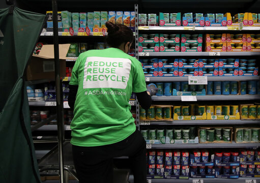 A member of staff stacks loose tins on the shelves in the UK supermarket Asda, as the store launches a new sustainability strategy, in Leeds