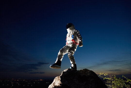 Full length of astronaut standing on one leg on top of mountain with beautiful night sky on background. Cosmonaut wearing white space suit with helmet. Concept of space travel and cosmonautics.