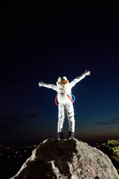 Back view of space traveler standing on top of rocky mountain and spreading hands in sides. Astronaut raising arms while looking at fantastic night sky. Concept of cosmonautics, space travel, freedom