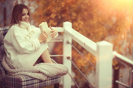girl in a knitted sweater reads a book on the veranda in the park, seasonal romance concept