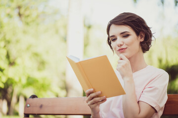 Photo sweet adorable interested lady sit bench read yellow book intriguing love adventure hero story peaceful lifestyle concept new knowledge exam preparation wear pink t-shirt park outdoors