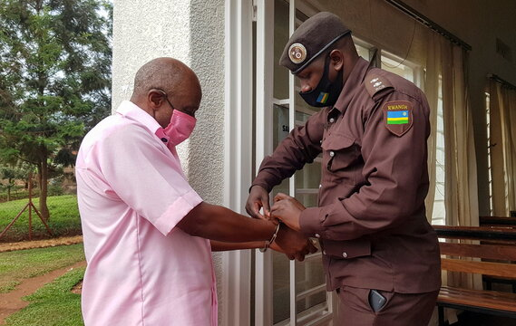 Paul Rusesabagina, portrayed as a hero in a Hollywood movie about Rwanda's 1994 genocide, has his handcuffs removed before entering the courtroom in Kigali