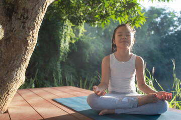 Child doing exercise healthy in sportive top and leggings practicing yoga at in nature. sitting in lotus pose on yoga mat meditating smiling relaxed with closed eyes, Mindfulness meditation concept.