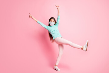 Full length photo of little lady dance raise hands fingers wear mask teal sweatshirt pants white sneakers isolated pink color background
