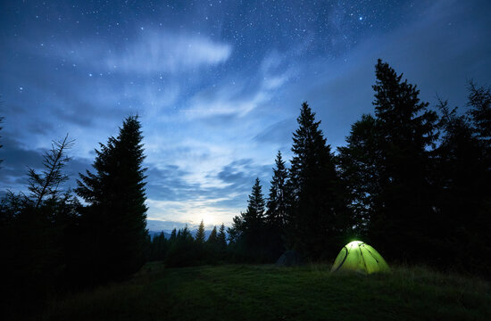 Horizontal snapshot of beautiful summer night in the mountains, magical sky full of stars over high tops of spruce trees and illuminated green tent in the middle of mountain glade. Night camping