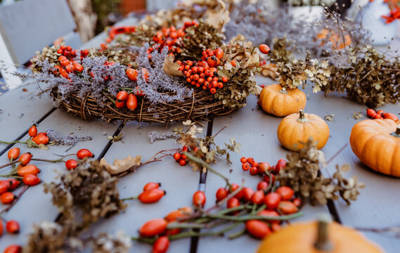 Making floral autumn door wreath from natural materials: colorful rosehip berries, rowan, dry flowers and pumpkins. Fall flower decoration workshop. Florist workplace.