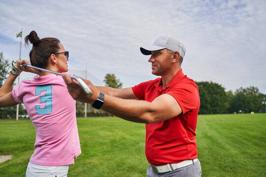Female golfer learning to make a backswing