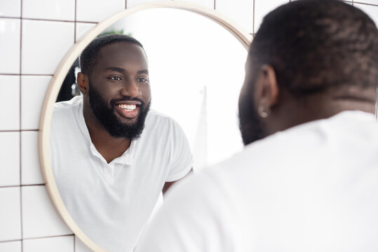 smiling afro-american man looking in mirror