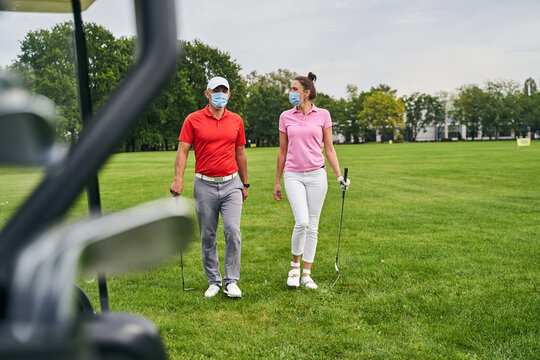 Two golfers in protective masks crossing the golf course