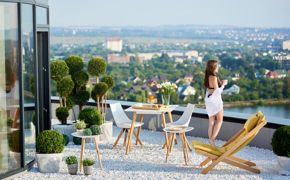 Back view of charming lady standing on rooftop terrace and looking at city. Smiling girl with long hair holding cup of coffee while spending time on hotel roof. Concept of relax, leisure and luxury.