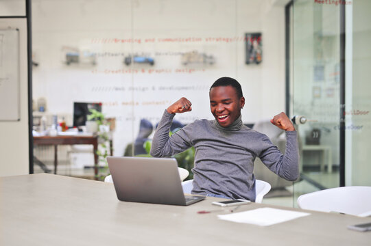 young man elated in front of a computer