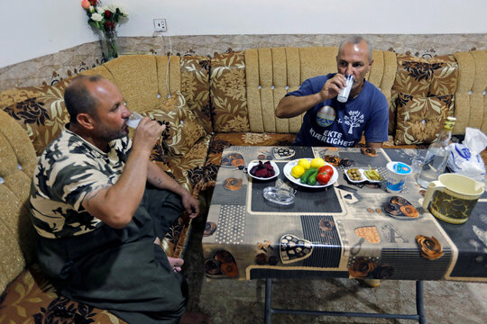 Saad Hussein an Iraqi Yazidi, drinks Arak with his brother which he produced out of dates on the outskirts of Mosul