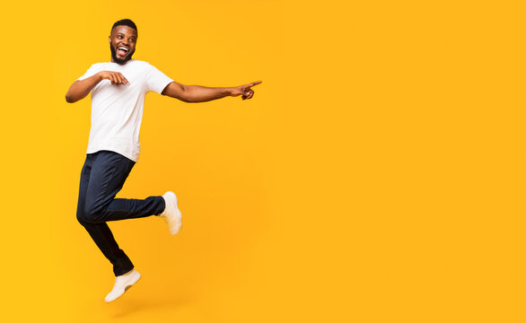 Joyful black guy jumping up and pointing aside
