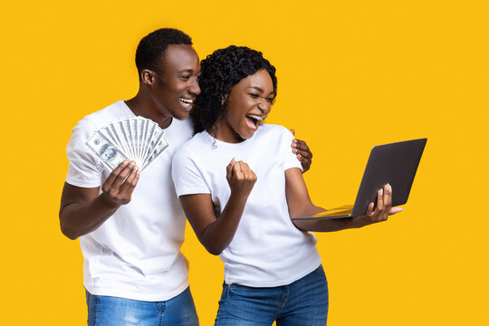 Emotional black couple celebrating win with laptop and cash