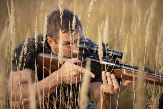 Close up image of male shooting rifle. Image taken during big game hunting trip. Hunting period, autumn season open.