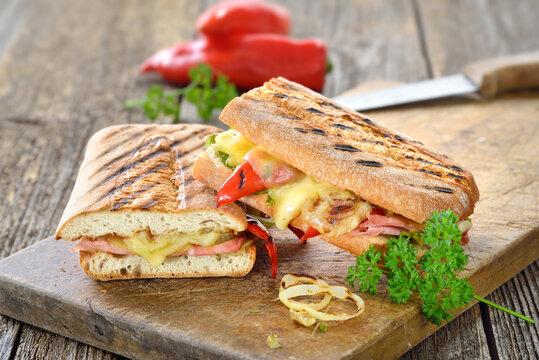 Getoastetes und im Kontaktgrill gepresstes italienisches Ciabatta mit Prosciutto, Käse und Grillgemüse  - Grilled Italian panini with ham, cheese and vegetables served on a wooden cutting board