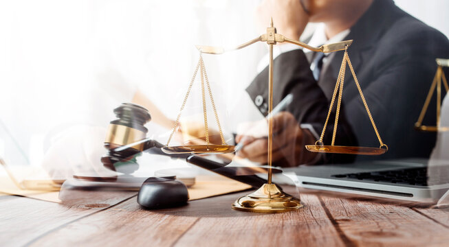 justice and law concept.Male judge in a courtroom on wooden table and Counselor or Male lawyer working in office. Legal law, advice and justice concept.