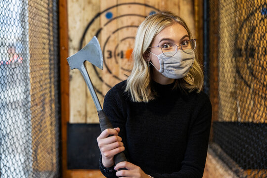 Teenage girl holds axe at an axe throwing range with target behind her