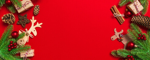 Wall Mural - Top view of Christmas decorations on red background. Banner New Year holiday concept with copy space
