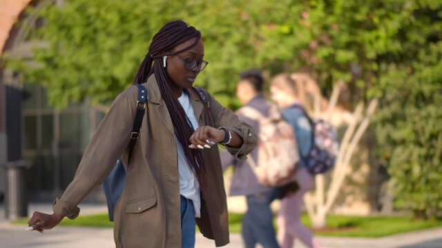 Young african female student late for classes running on university campus