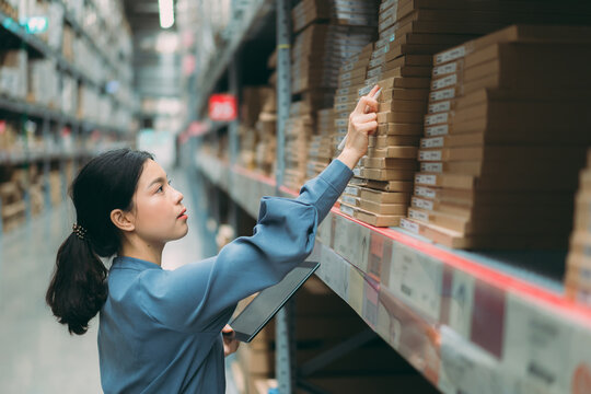 Young energetic smart Asian business working woman smile while using digital tablet to check goods on shelves for product management in warehouse, Logistics business planning concept with copy space