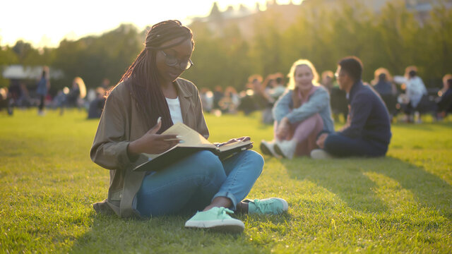 Happy african student lady reading book outdoors in park