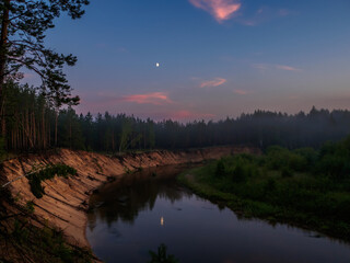 The clear evening sky and the Moon is reflected in the mirror surface of the forest river at sunset. Silence at sunset on the high bank of the forest river.