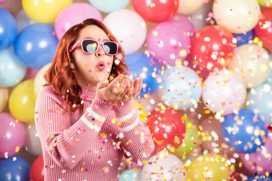 Happy young woman blowing confetti. Redheaded girl party alone on colorful balloons background