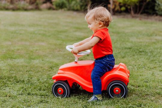 Baby girl riding toy car in garden