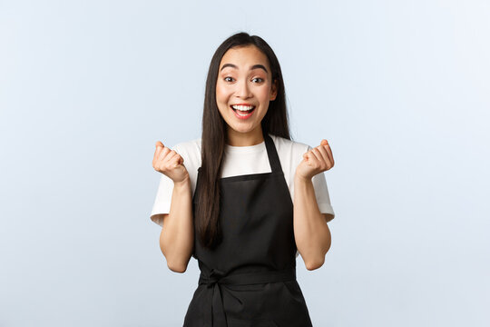 Coffee shop, small business and startup concept. Cheerful asian girl winning, best employee month, fist pump and rejoicing. Happy barista jumping enthusiastic, winning competition