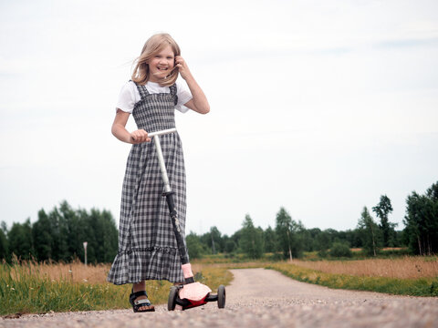 Portrait of a girl with a scooter in the village