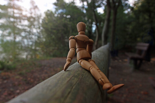 Close up along timber and focus on foreground of a wooden mannequin sitting on a beam, relaxing in quiet lonely forest