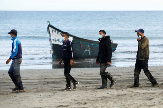 Several migrants walk near a boat on Maspalomas beach after dozens of migrants arrived at the south of the island of Gran Canaria