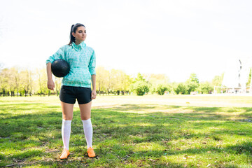 Young female soccer player standing on field holding ball.