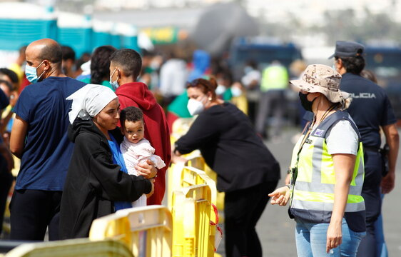 A migrant woman with her baby talks to a police member after dozens of migrants arrived at the south of the island of Gran Canaria