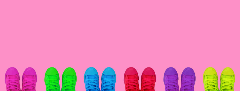 Multicolored bright sneakers on a bright pink background.Copy space