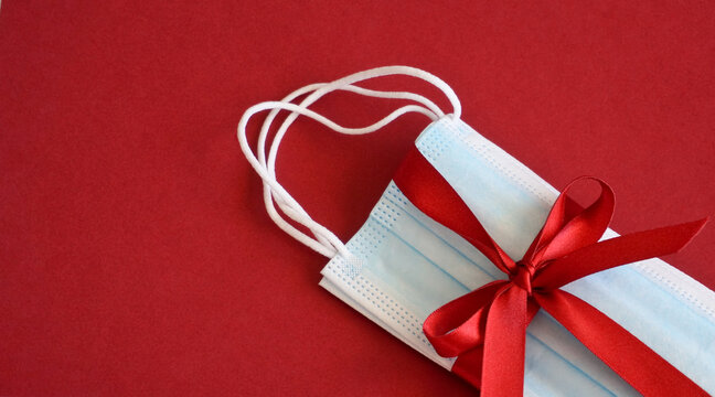 Surgical face mask with red ribbon as a present on colorful background